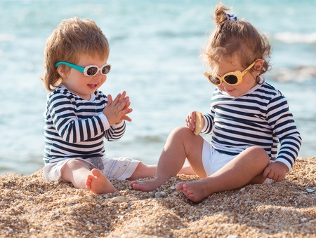 38371841 - little boy and girl playing on the beach